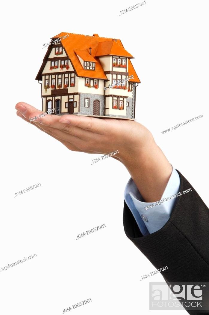Stock Photo: Human hand showing a model house.