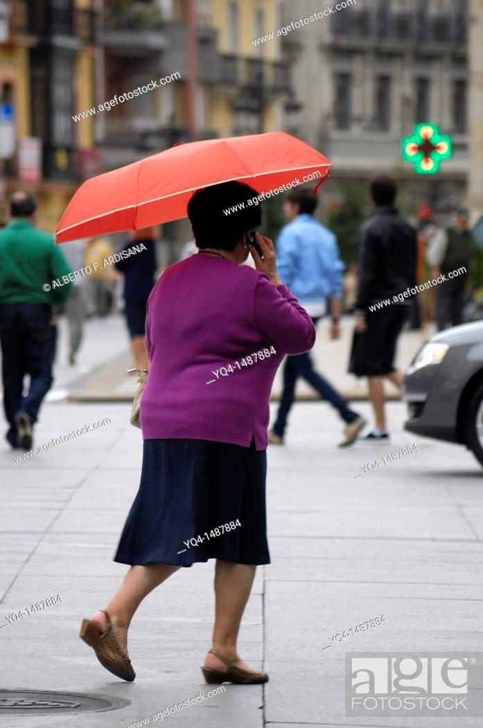 Stock Photo: Lady with umbrella on a rainy day in Aviles, Asturias, Spain.