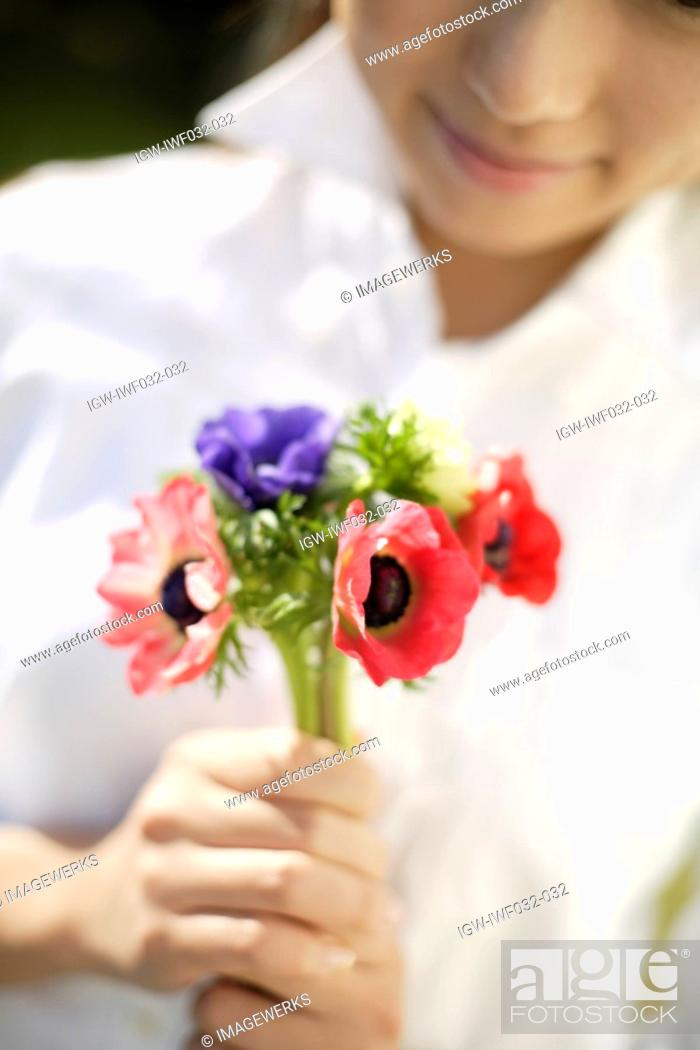 Stock Photo: Woman with flowers in foreground.