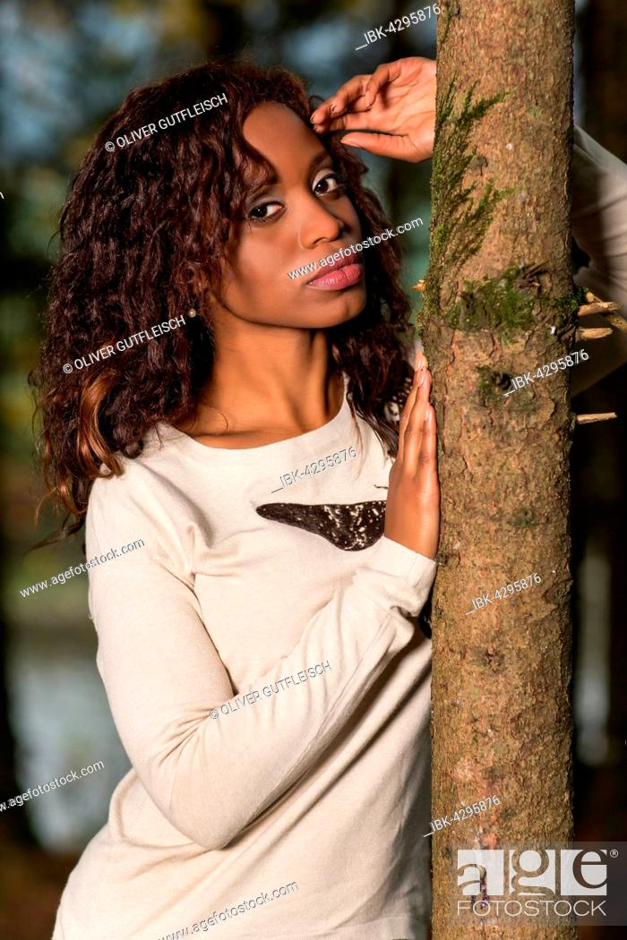 Stock Photo: Dark-skinned young woman in autumn outfit in the forest.