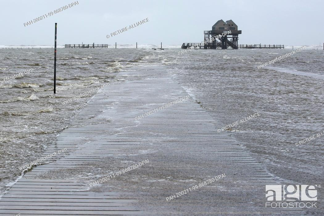 Stock Photo: dpatop - 11 February 2020, Schleswig-Holstein, St. Peter-Ording: Rising water floods the beach of St. Peter-Ording. In the afternoon a storm surge is expected.