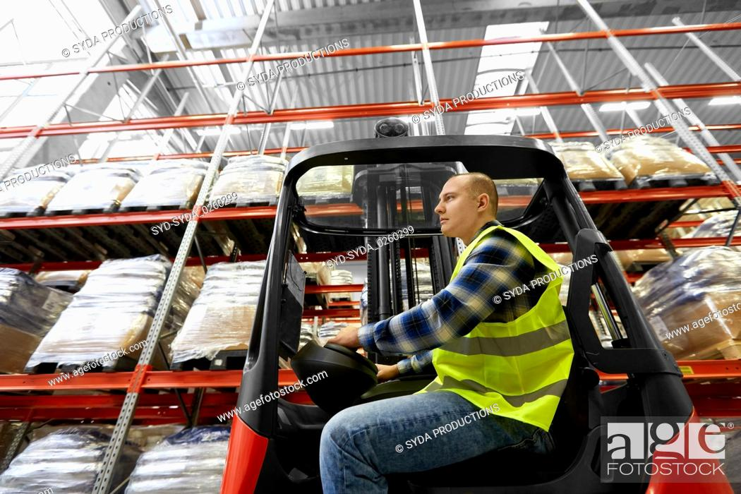 Stock Photo: male worker driving forklift loader at warehouse.