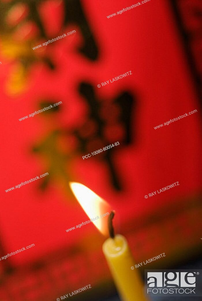 Stock Photo: Close-up of lit candles, red poster asian characters on it blurred in background.