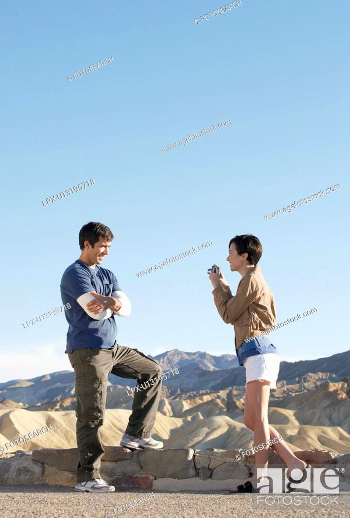 Stock Photo: Woman photographing man by stone wall in desert, Death Valley, California, USA.