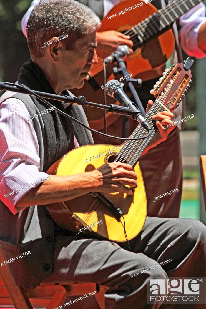 Stock Photo: canarian guitarist seated playing the bandurria or lute-type instrument accompanied by a man standing playing the spanish guitar.