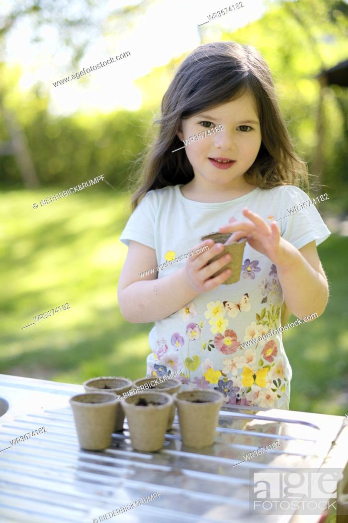 Stock Photo: Cute girl planting seeds in small pots on table at yard.