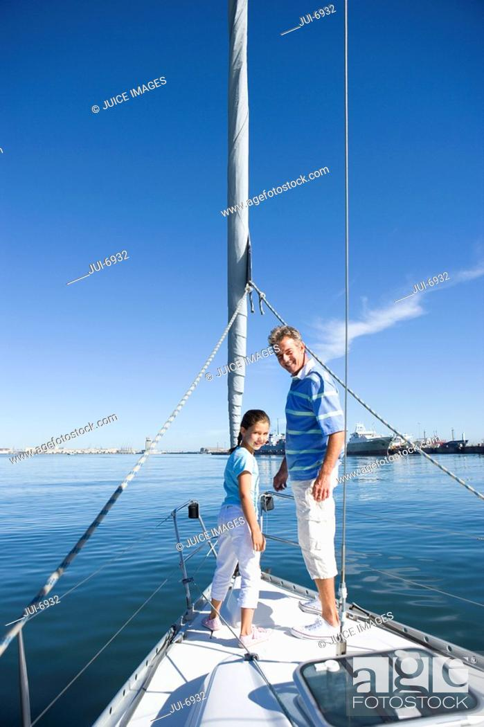 Stock Photo: Father and daughter 8-10 standing at bow of sailing boat, smiling, side view, portrait.