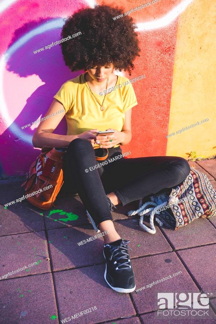 Stock Photo: Young woman with afro hairdo sitting at graffiti wall and using smartphone.