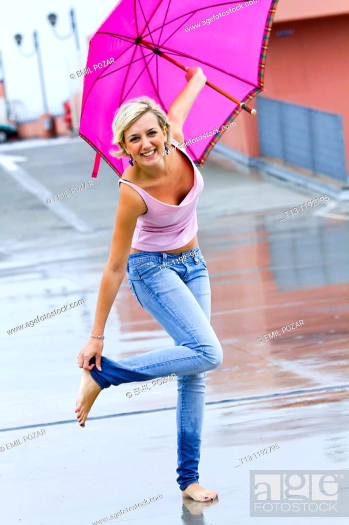 Stock Photo: Young woman, wet legs and raining season.