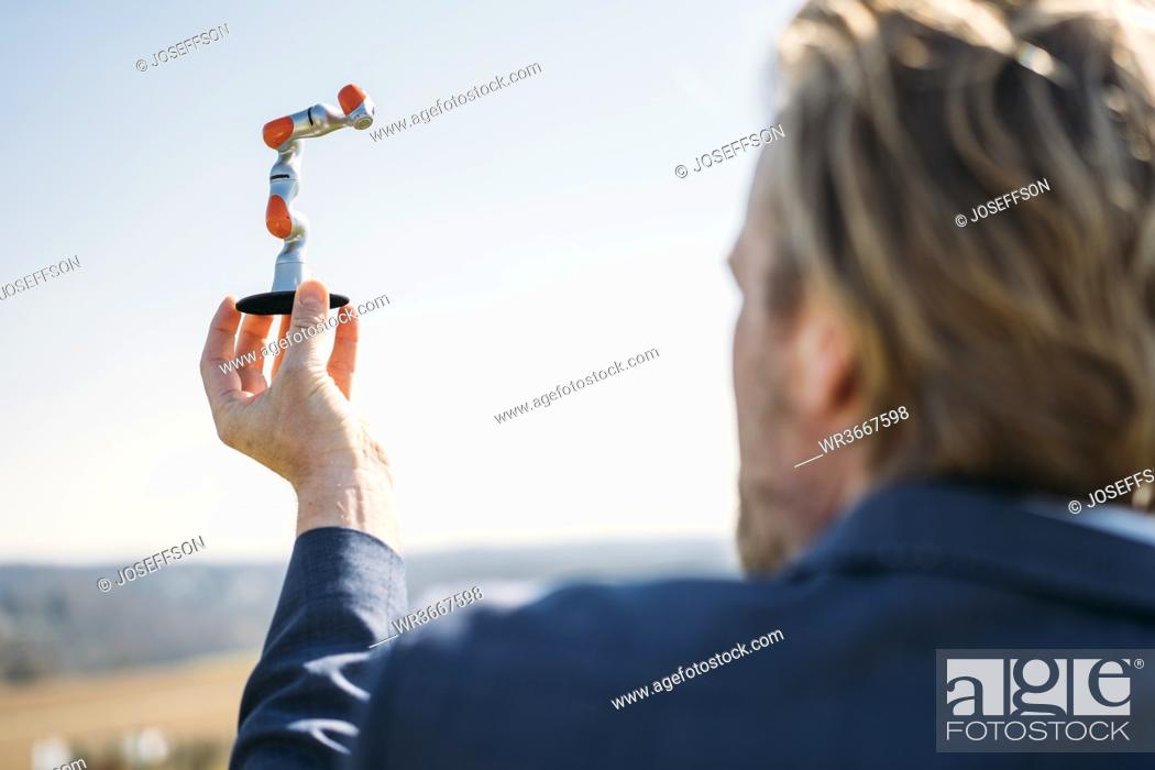 Stock Photo: Businessman holding at small robotic arm against clear sky on sunny day.