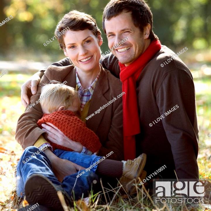 Stock Photo: A young family sitting on the grass in autumn time.