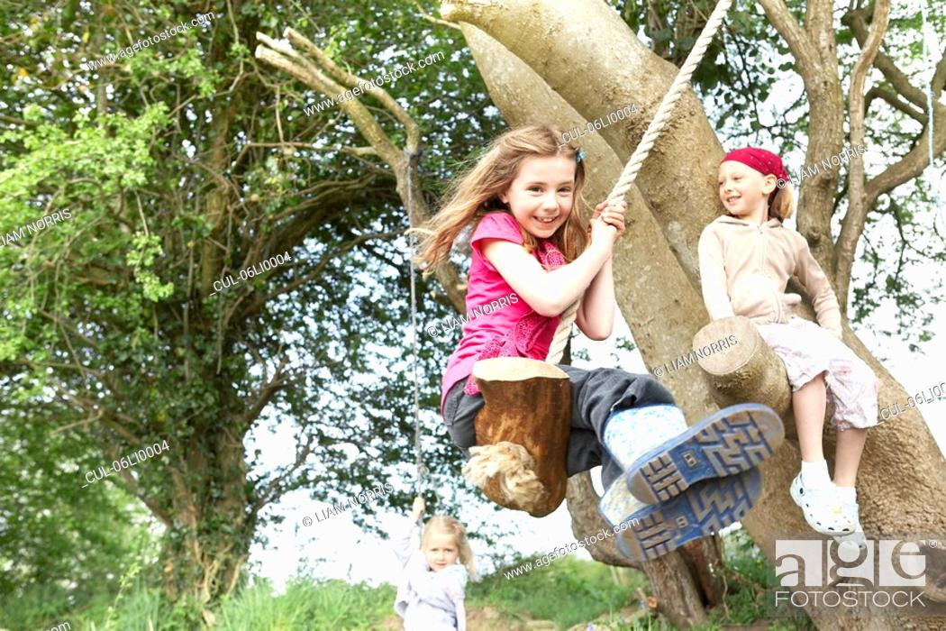 Stock Photo: Young girl on rope swing.