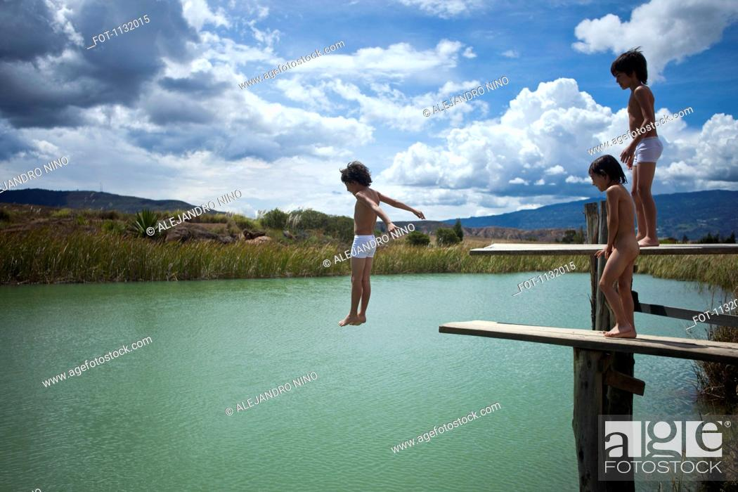 Stock Photo: A boy jumping into water while his twin brother and friend watch.
