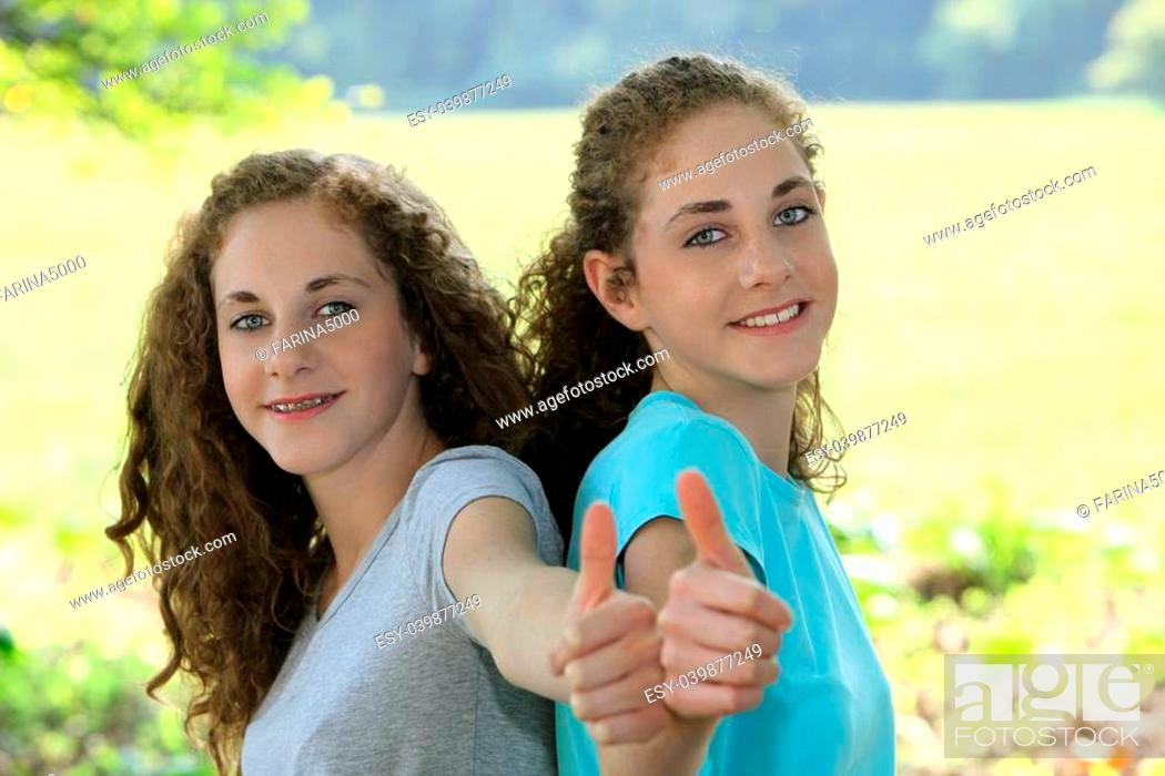 Stock Photo: Smiling beautiful young teenage sisters giving a thumbs up of approval as they enjoy a day outdoors in the sunshine during their summer vacation.