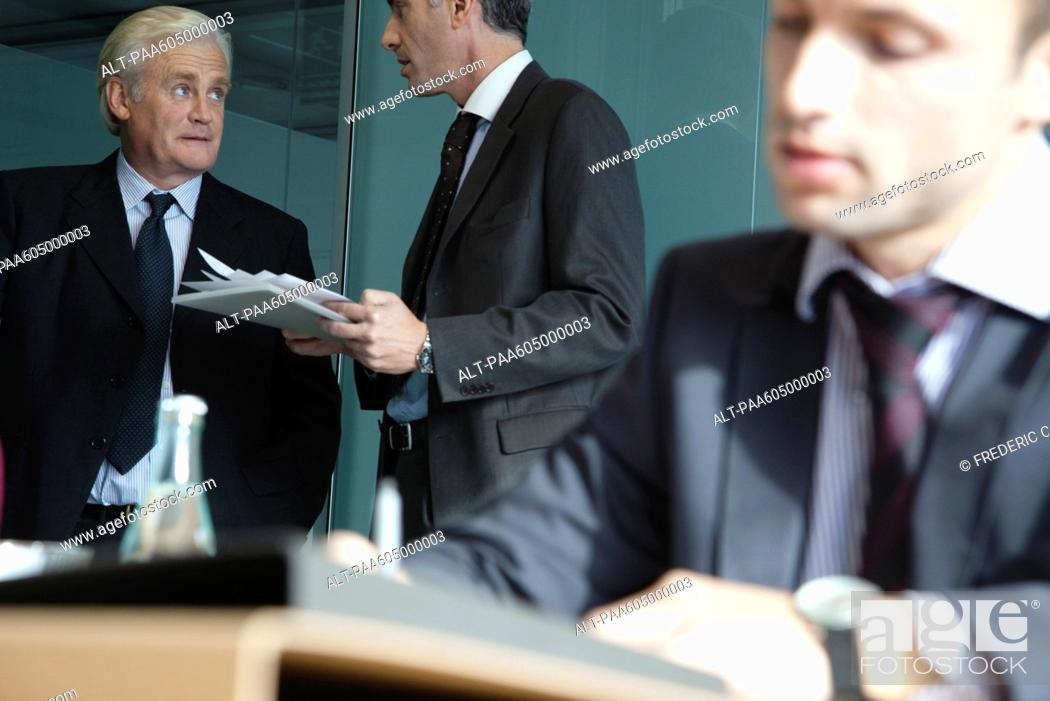 Stock Photo: Executive in discussion, young businessman working in foreground.