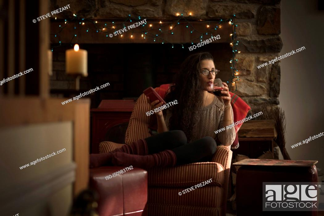Photo de stock: Young woman relaxing in armchair drinking red wine.