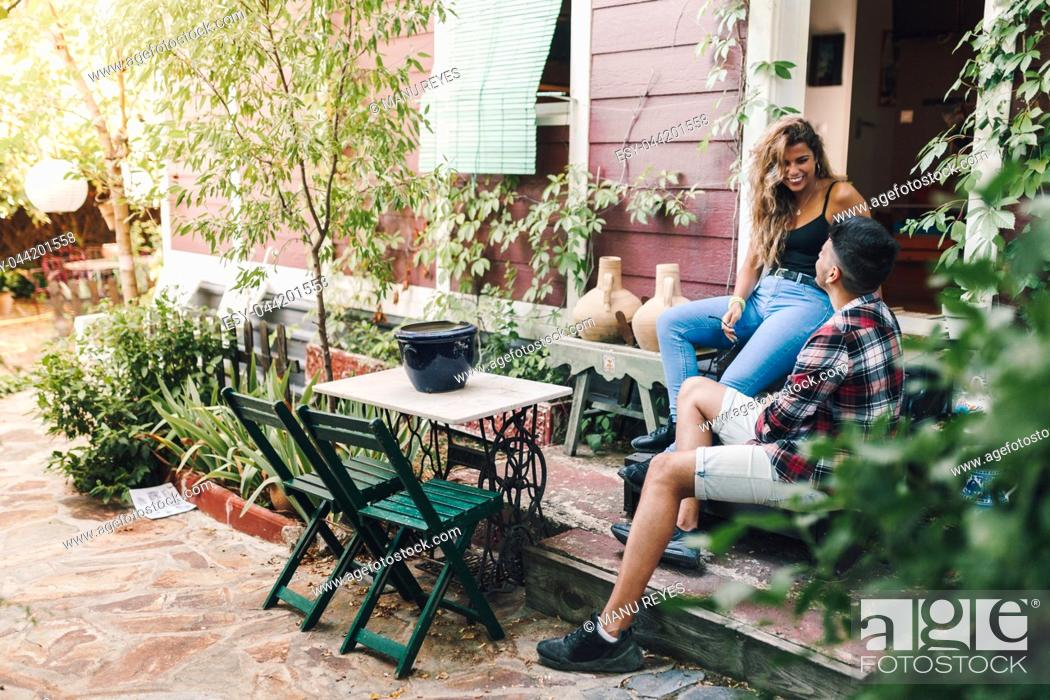 Photo de stock: Smiling young couple sitting in the garden chairs near their wooden house with their smart phone.