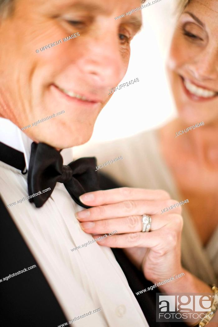 Stock Photo: Close up of woman adjusting bowtie of manís tuxedo.