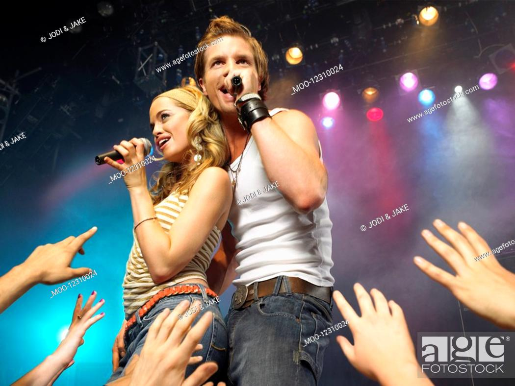 Stock Photo: Young man and woman singing on stage in concert in front of adoring fans low angle view.