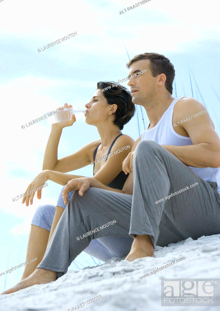 Stock Photo: Couple sitting in exercise clothing on beach, woman drinking water.