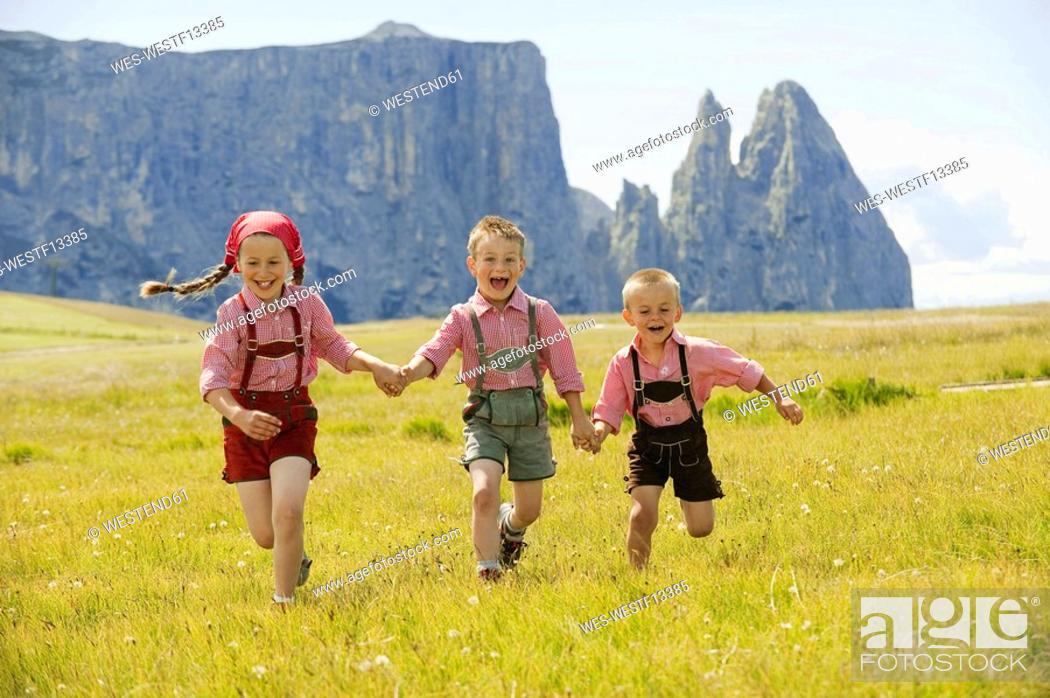 Stock Photo: Italy, Seiseralm, Three children 4-5, 6-7, 8-9 running in field.