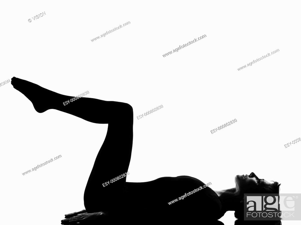 Stock Photo: woman exercising lying on back fitness yoga stretching in shadow grayscale silhouette full length in studio isolated white background.