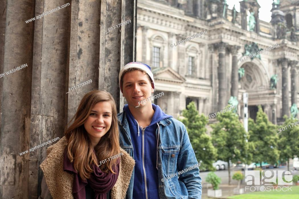 Imagen: Portrait of smiling young friends standing by column at Altes Museum against Berlin Cathedral.