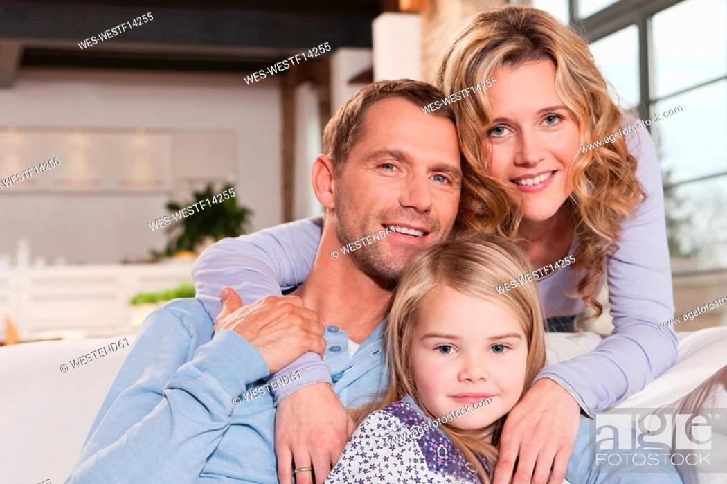 Stock Photo: Germany, Cologne, Family sitting on sofa, smiling, portrait, close-up.