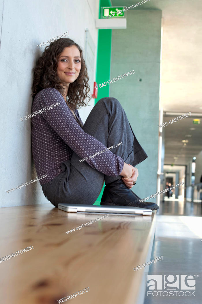 Stock Photo: Germany, Leipzig, Young woman sitting with laptop, smiling, portrait.