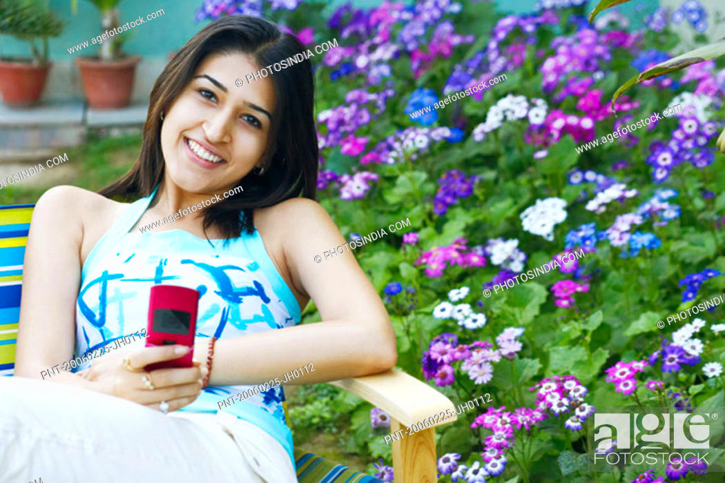 Stock Photo: Portrait of a young woman holding a mobile phone.