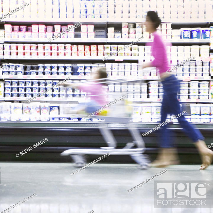 Stock Photo: Blurry woman with daughter in grocery cart.
