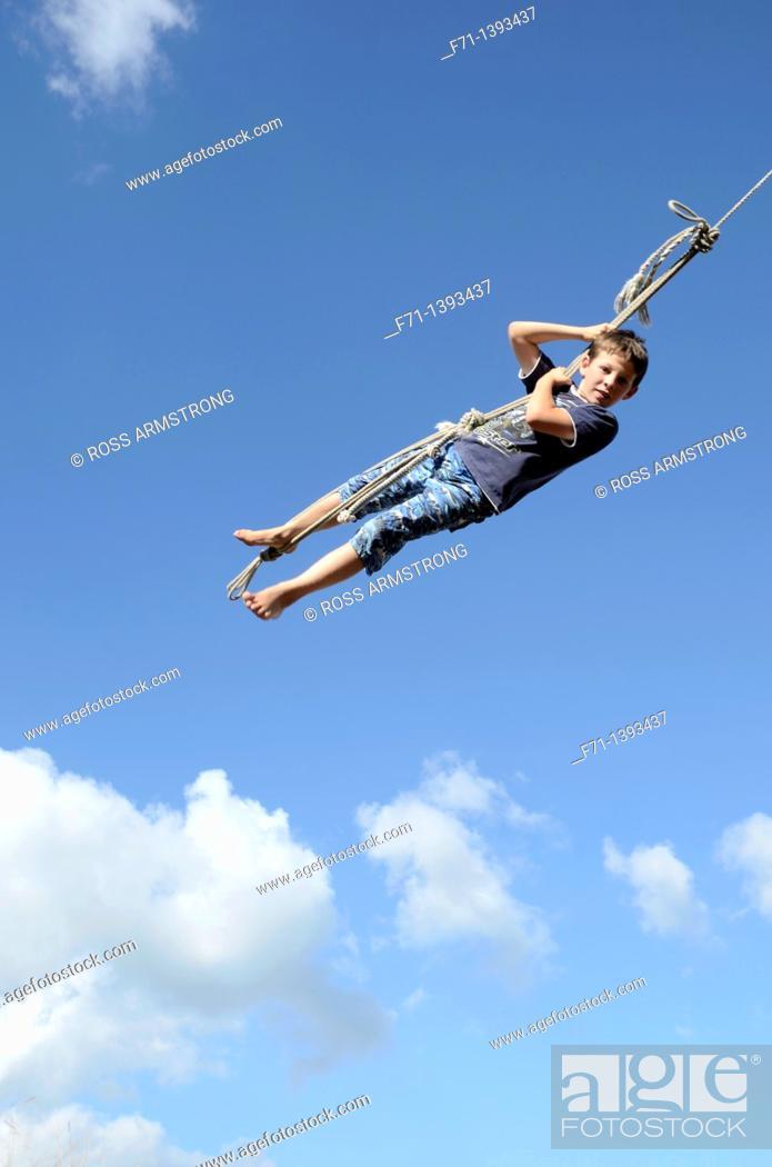 Stock Photo: Nine year old boy swinging on a rope swing Atiamuri, New Zealand.
