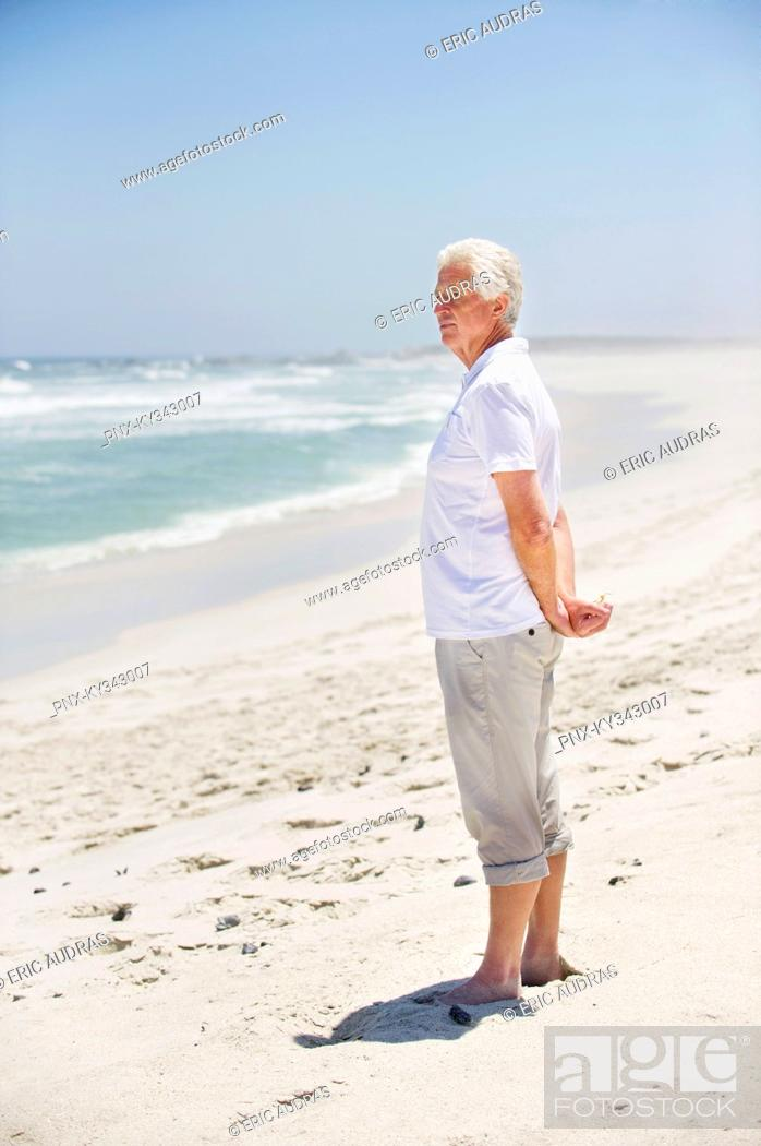 Stock Photo: Side profile of a senior man standing on the beach.