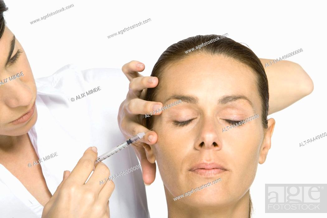Stock Photo: Woman receiving Botox injection, eyes closed.