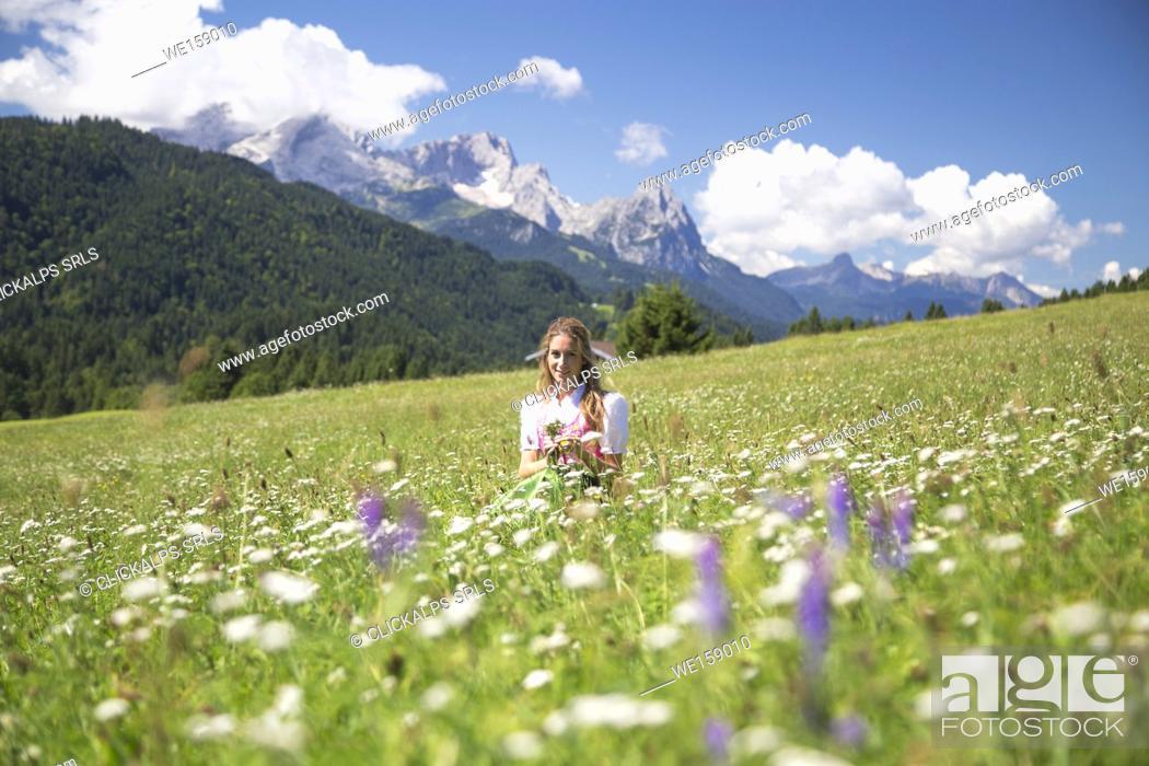 Stock Photo: A girl in typical dress into the alpine landscape of GErold, Garmisch Partenkirchen Land, Bayern, Germany.