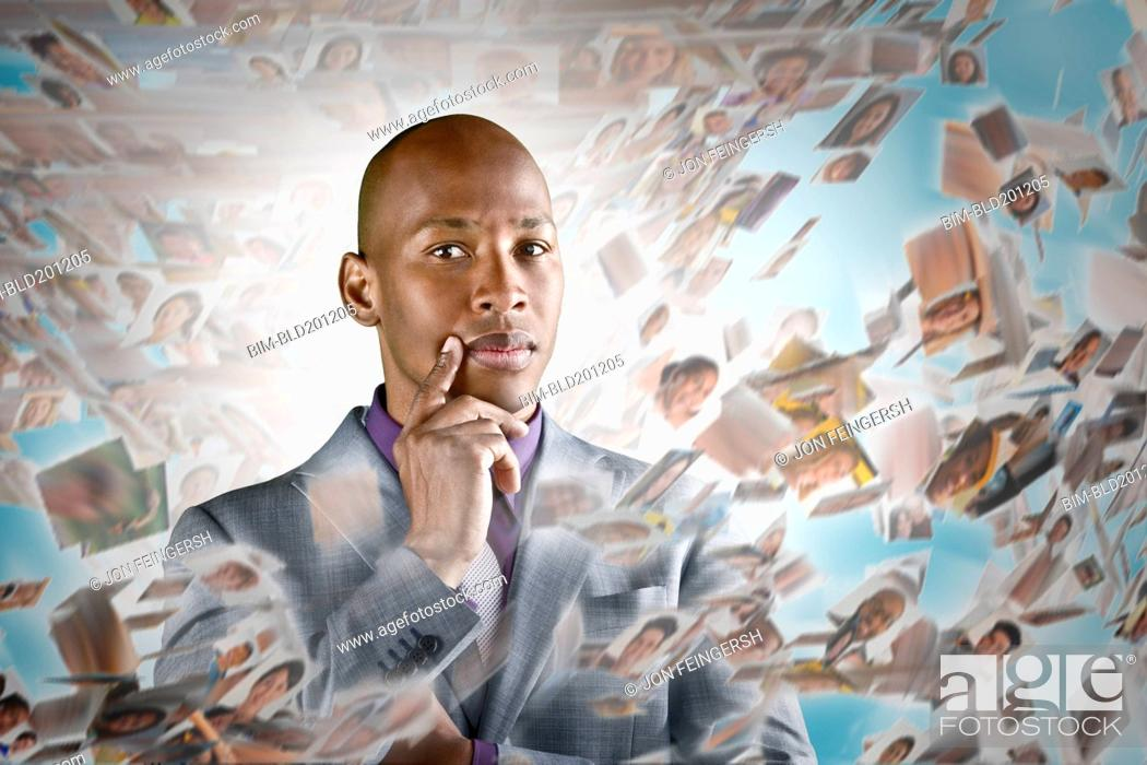 Stock Photo: African American businessman surrounded by images of business people.