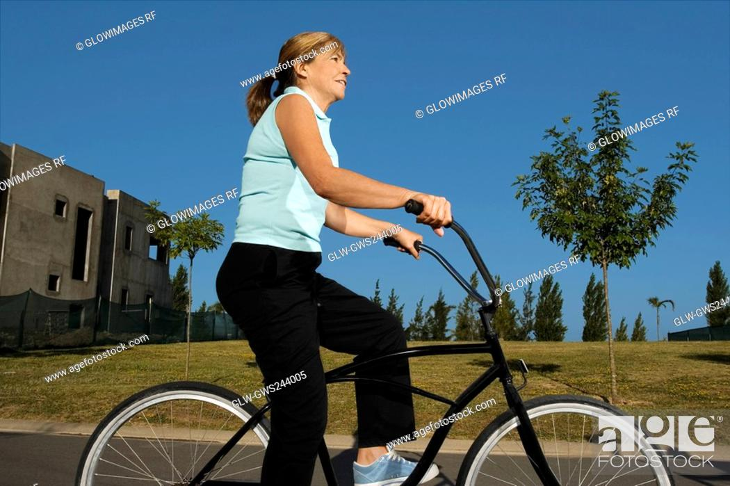 Stock Photo: Side profile of a senior woman cycling.
