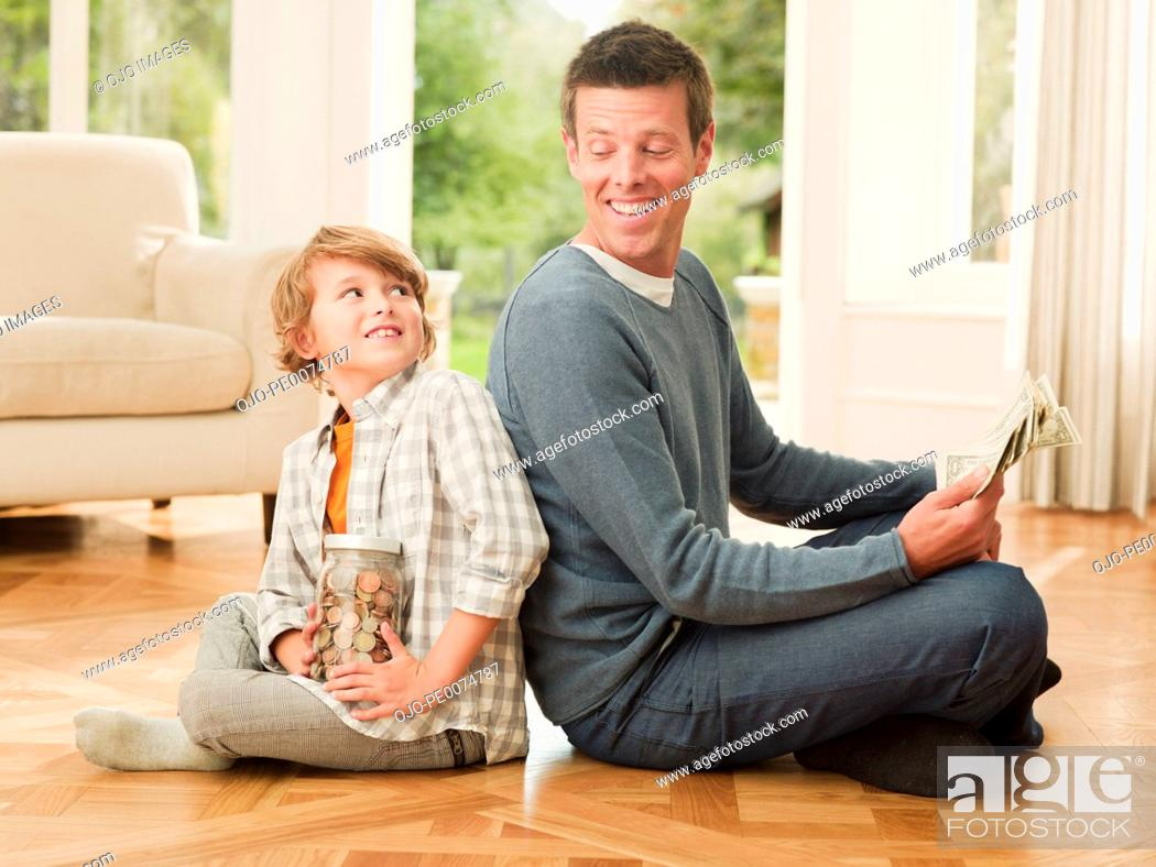 Stock Photo: Father and son holding money sitting back to back.