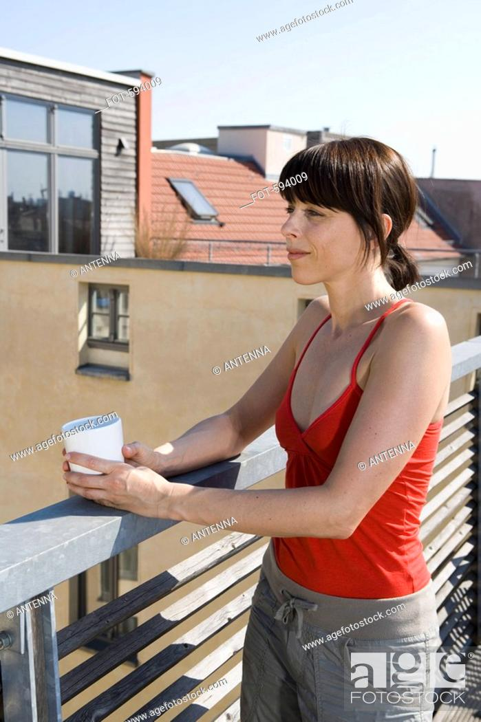 Imagen: A woman standing on a rooftop terrace with a cup.