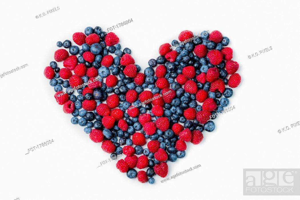 Stock Photo: Blueberries and raspberries arranged in heart shape.