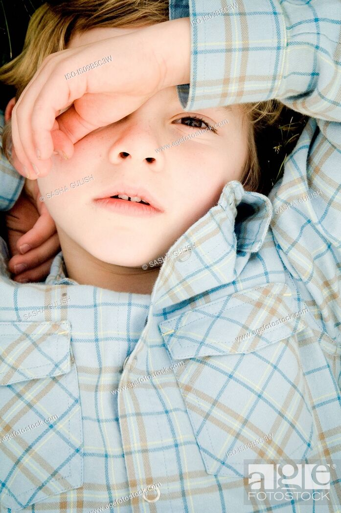 Stock Photo: Overhead portrait of boy covering eye with hand.