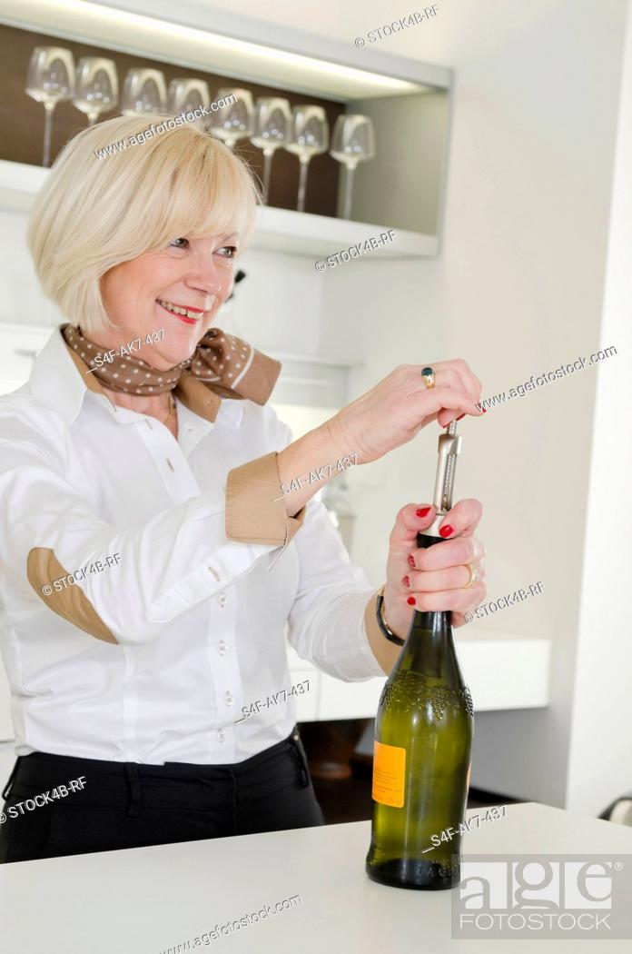 Stock Photo: Senior woman in kitchen opening bottle of Prosecco.