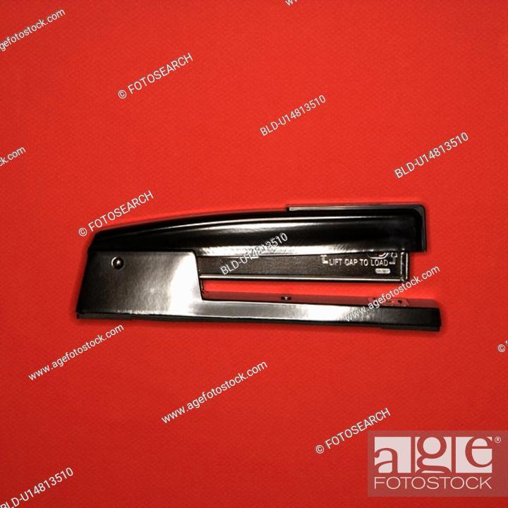 Stock Photo: Black stapler on red background.