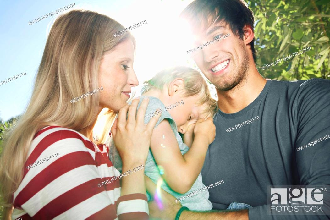 Stock Photo: Germany, Cologne, Parents carrying tired son, close up.
