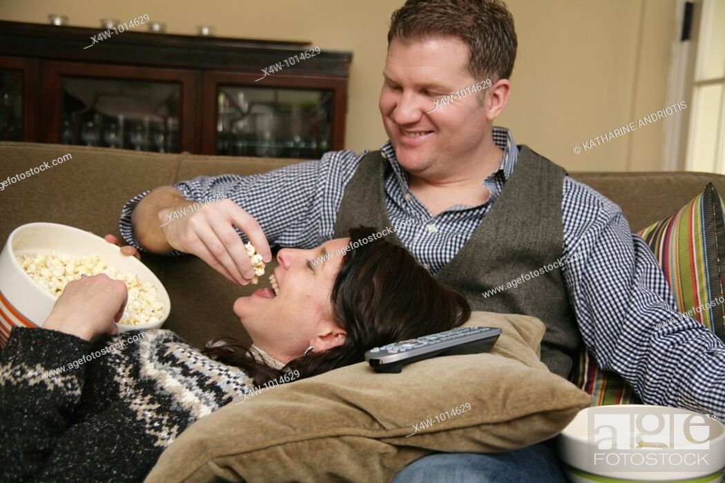 Stock Photo: Snacking while lounging on the sofa at home is a fun pastime of otherwise busy couples  Pictured here is a man feeding popcorn to his wife as she lays her head.