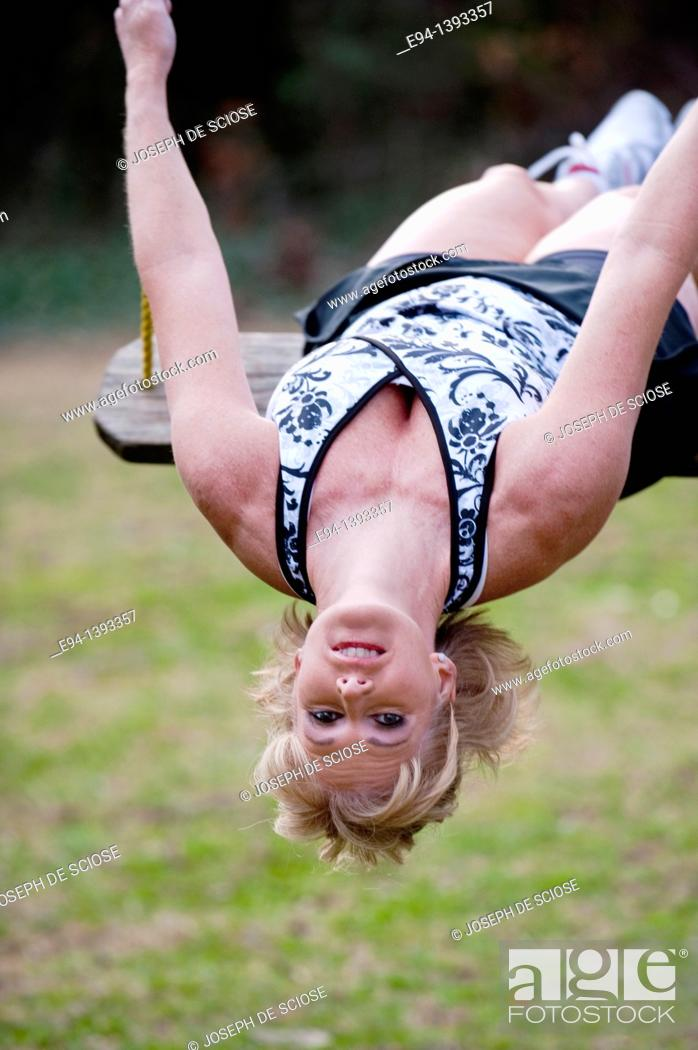 Stock Photo: Fifty year old blond woman in fitness attire playing on a rope swing outdoors.