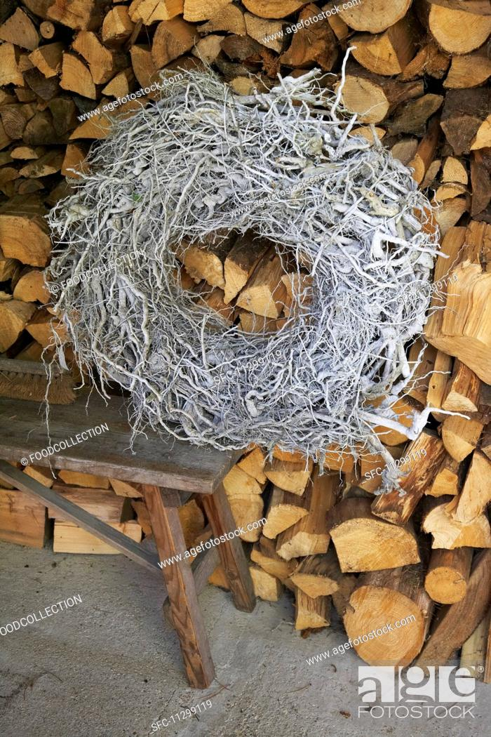 Stock Photo: A woven wreath on a bench against a wood pile.