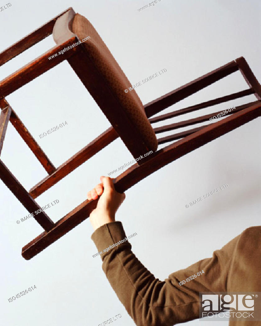 Stock Photo: Young man holding a chair.