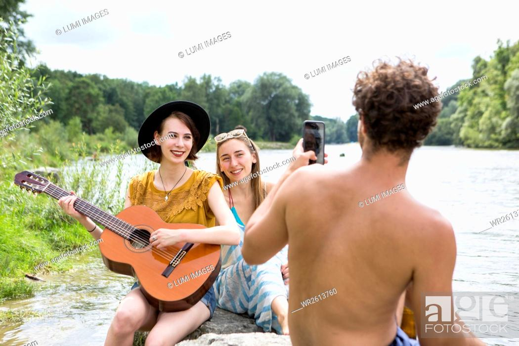 Imagen: Group of friends relaxing on the riverbank.