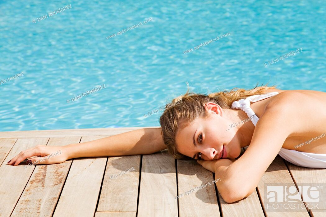 Stock Photo: Blonde beautiful woman resting and lying down by the pool.